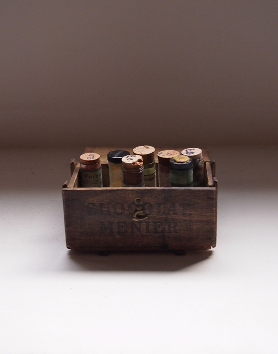 古いチョコレートの箱に顔料のビン